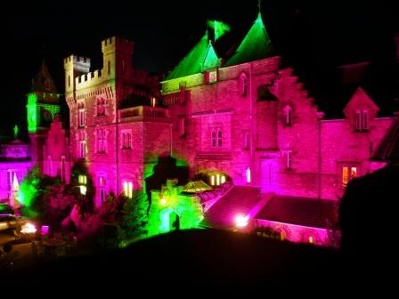 Craig y Nos Castle lit at night purple, green, yellow lighting for Halloween Fright Night, Swansea, Wales