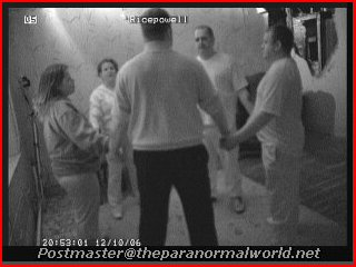 Ghost Hunters in Wales stand holding hands haunted house seance Craig y Nos Castle John Mellon room